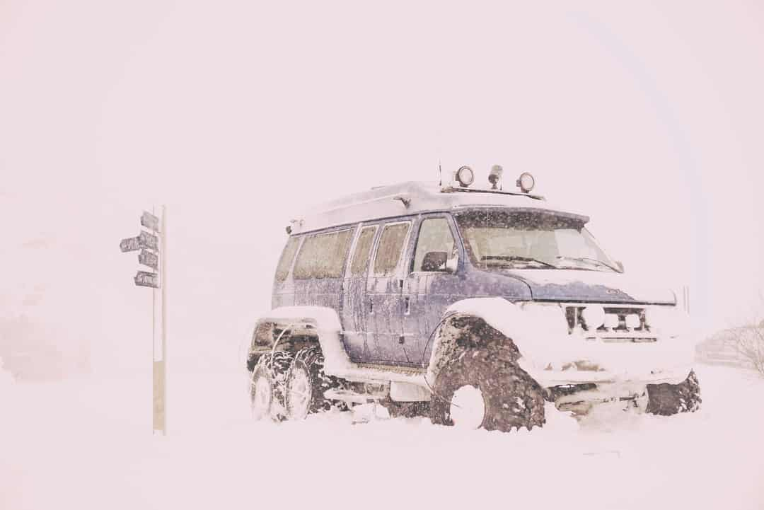 A truck parked on the side of a snow covered field
